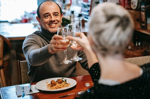 Couple having date in restaurant while clinking wineglasses