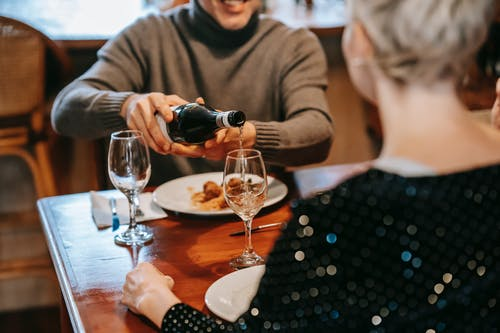 Crop unrecognizable couple having dinner in light room while male pouring wine in glasses at table with plate with pasta with meatballs