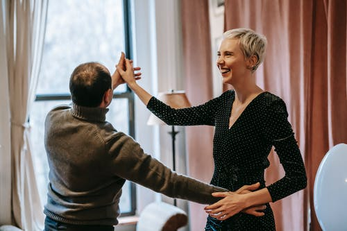 Happy couple holding hands while dancing in room near window