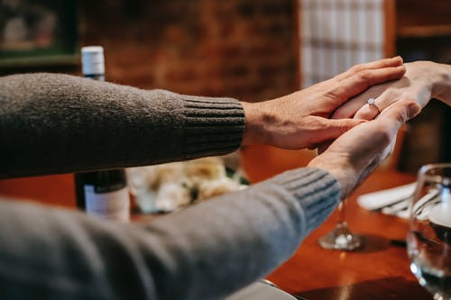Unrecognizable couple having date in restaurant and holding hands