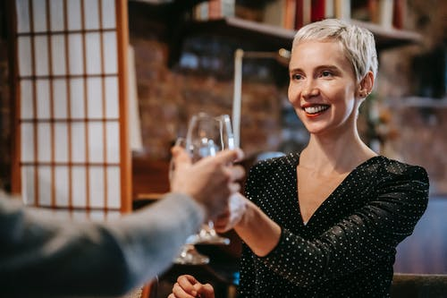 Positive couple having date in restaurant while clinking wineglasses
