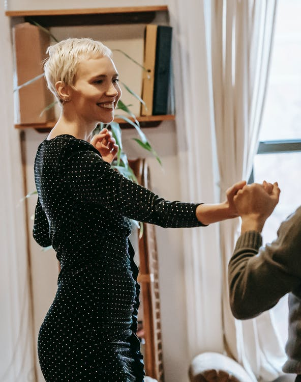 Smiling couple dancing and holding hands in light room near curtains on windows and green plant near shelves