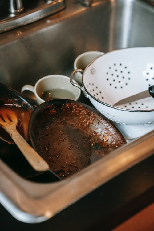 High angle heap of dirty dishes placed in sink after cooking in kitchen