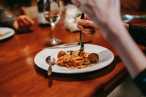Crop anonymous female enjoying tasty yummy spaghetti with meat ball and glass of white wine in restaurant