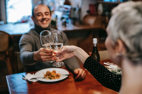 Happy couple clinking wineglasses in restaurant
