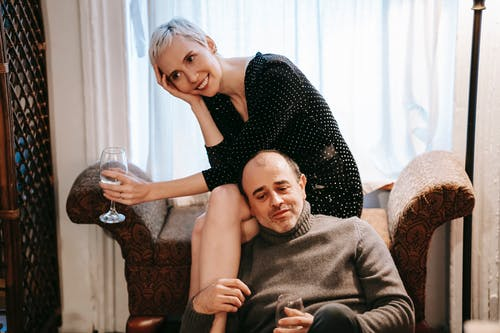 Cheerful couple relaxing on couch with wineglasses