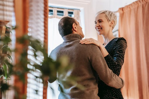 Happy adult couple moving slowly in romantic dance while enjoying romantic moment at home