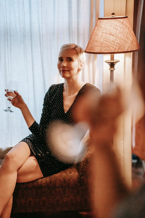 Relaxed female with short hairstyle holding wineglass and resting on settee near window and blurred silhouette of partner hand in foreground