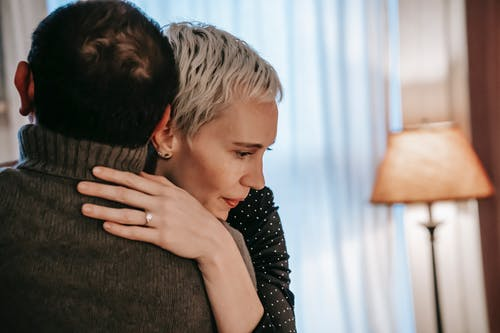 Happy female hugging gently with man while spending time together in modern apartment with cozy interior