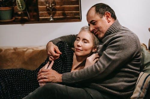 Loving couple cuddling tenderly sitting on sofa