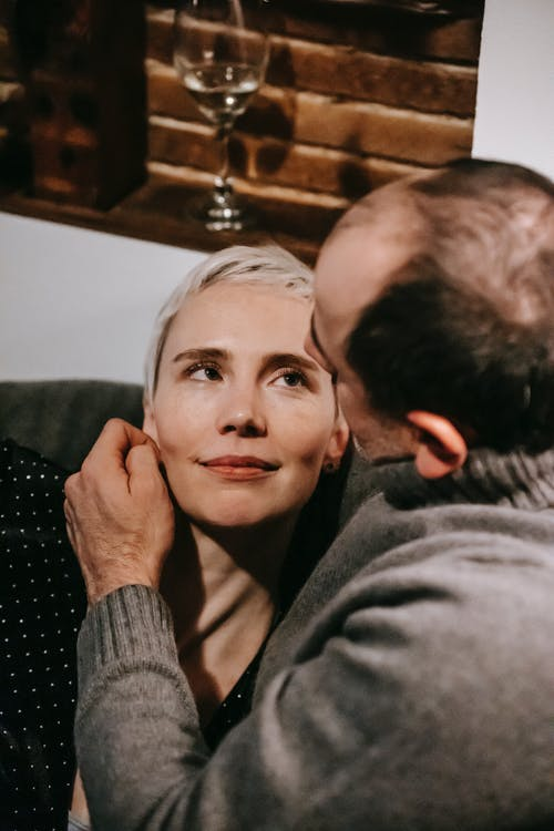 Husband gently stroking face of wife