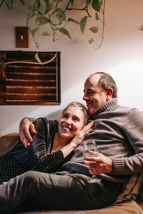Positive man with glass of drink cuddling smiling wife lying on couch and enjoying pleasant time together