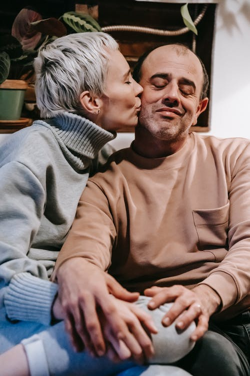 Gentle wife kissing cheek of adult husband sitting close with closed eyes while spending time together