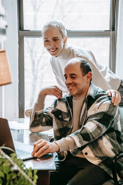 Cheerful woman standing behind man working on laptop