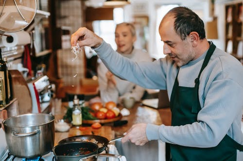 Man in Green Apron Holding Silver Spoon