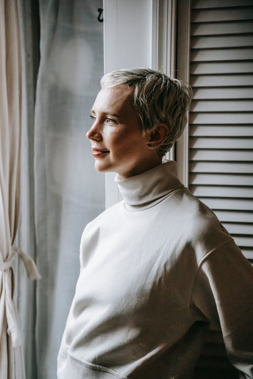 Serene dreamy woman with short dyed hair standing near window and gently smiling while looking away