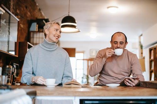 Man in Gray Sweater Drinking from White Ceramic Mug