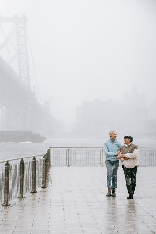Couple walking on embankment near river and bridge in winter