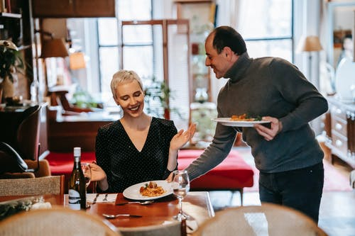 Positive adult couple having date and man serving plates with pasta for woman at table with bottle near wineglasses and cutlery