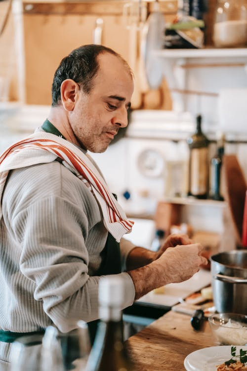 Thoughtful man in apron cooking dish on counter in kitchen