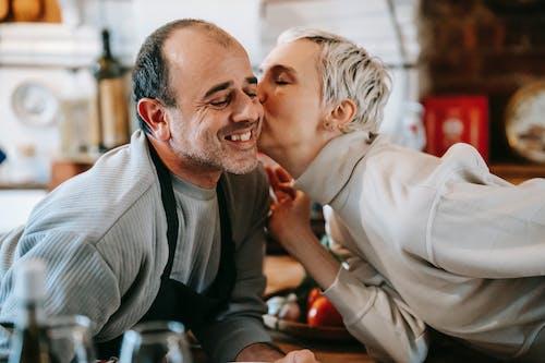 Man in Gray Suit Jacket Hugging Woman in Gray Blazer