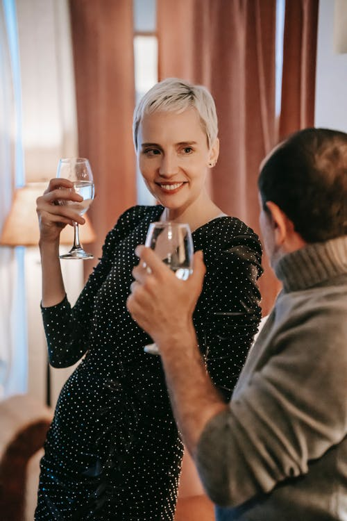 Positive couple with wineglasses in room