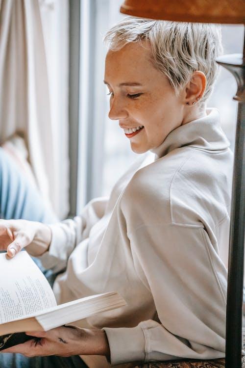 Smiling woman reading book lying on windowsill