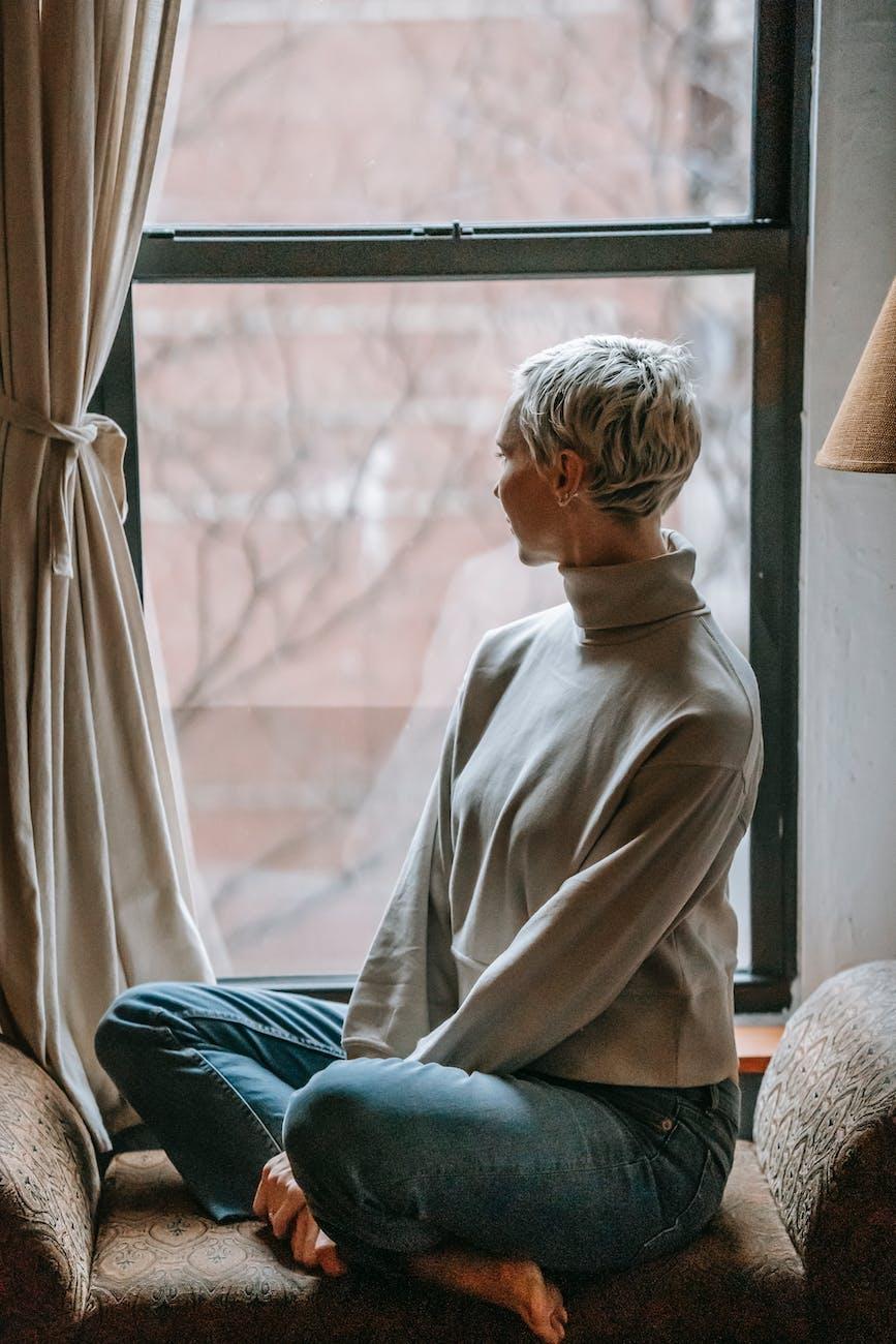 Une femme regardant par la fenêtre.   Photo : Pexel