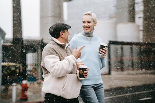 Woman in Gray Sweater and Blue Denim Jeans Holding White Ceramic Mug