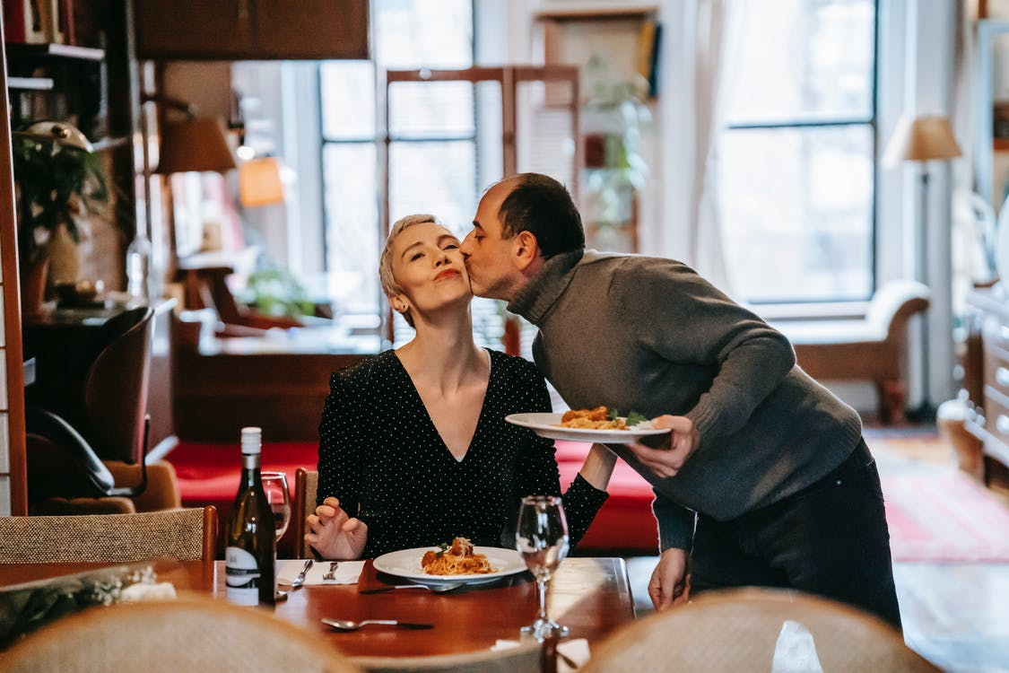 Gentle husband with plate of meal kissing wife having romantic dinner with bottle of wine at home