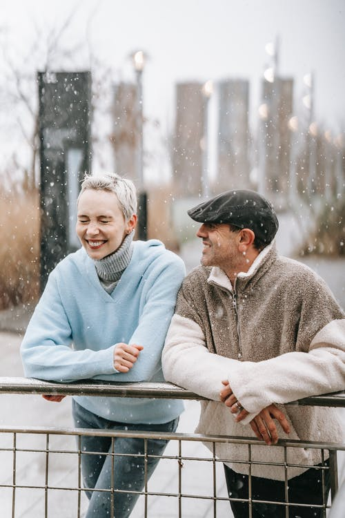 Glad woman with closed eyes and bright smile standing near man leaning on railing in winter park