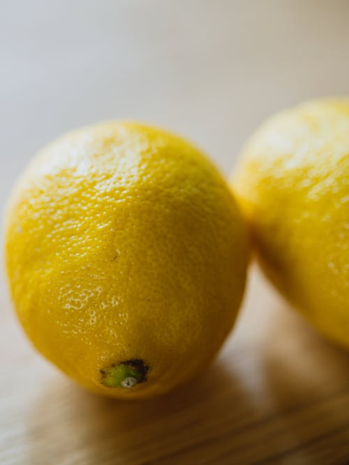 From above of ripe whole sour citrus lemons placed on wooden table in light room on blurred background in kitchen