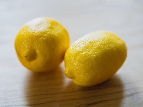 Ripe sour whole lemons placed on wooden surface in light room in kitchen with sunlight at home during harvest season