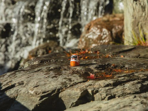 Japanese Daruma doll on stony rough terrain on blurred background of shiny waterfall