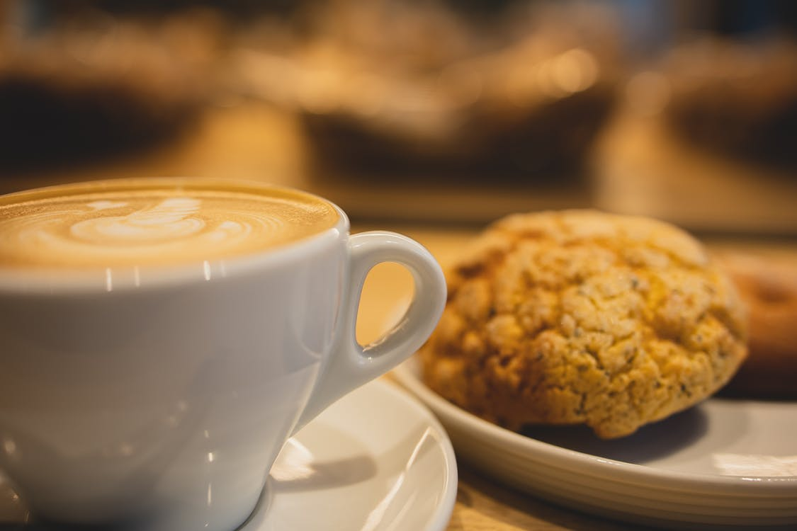 Mug of tasty fragrant coffee with latte art served near plate with oatmeal cookies on table on blurred background