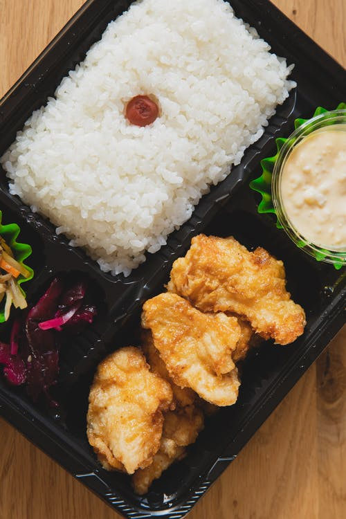 Top view of dish with rice and deep fried chicken pieces served in plastic takeaway container on table