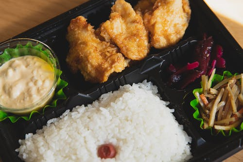 From above of plastic container with fried chicken and rice with sauce near sauce and sliced vegetables
