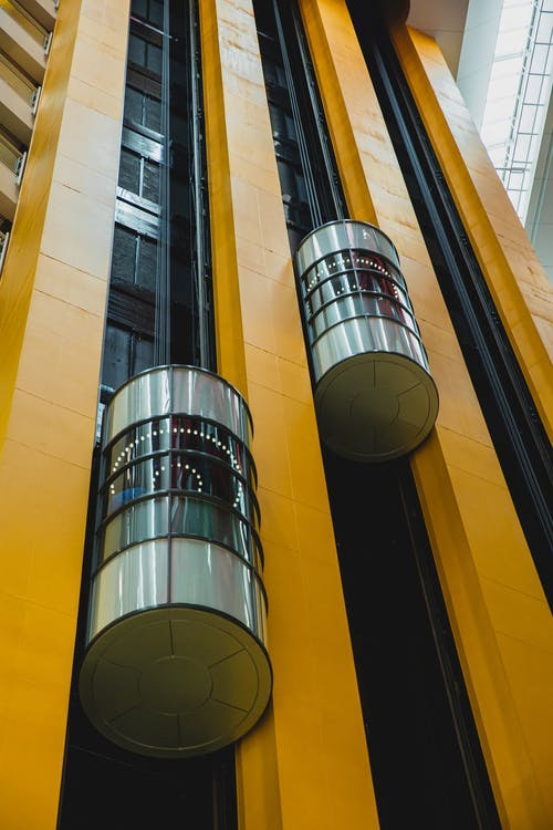 From below inside of high geometric modern multistory complex with round shaped lifts