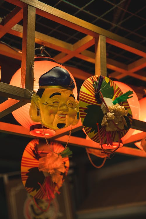 Traditional Chinese lanterns and mask hanging on metal bar