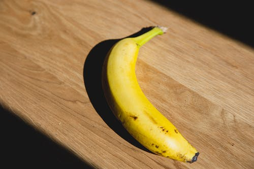 From above of ripe banana casting shadow placed on wooden board lightened by sunlight