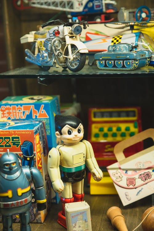 Collection of assorted toys including robots motorcycle and tank for sale in Japanese store
