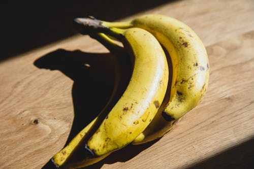 Ripe bananas placed on wooden table in sunlight