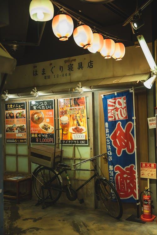 Shining Chinese lanterns above bike parked near cafe