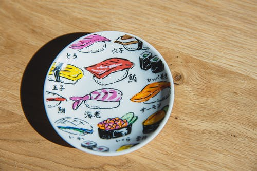 Top view of white ceramic plate with colorful drawings of sushi and rolls placed on wooden table