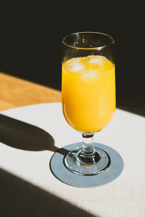 From above of crystal glass of cold refreshing orange juice placed on table
