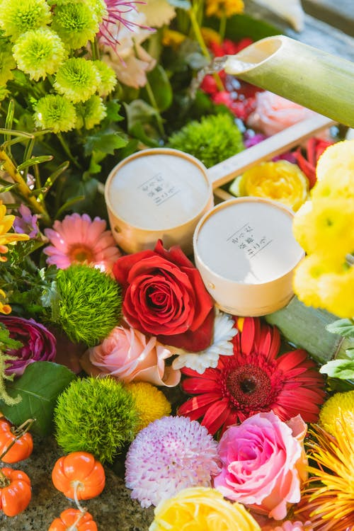 Japanese water basin with bamboo pipe and ladles decorated with colourful fresh flowers