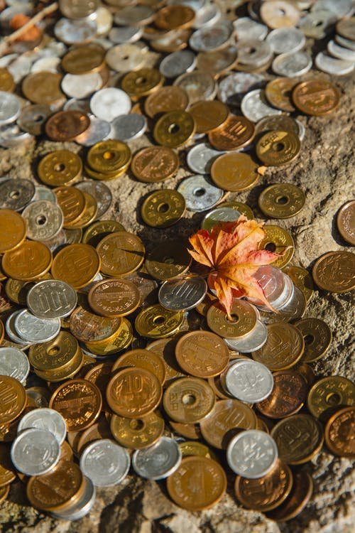 High angle of various golden and silver coins scattered on rough stone surface with small red leaf in sunny day in fall