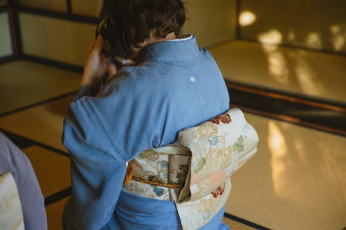 Back view of unrecognizable person wearing authentic robe sitting on tatami while drinking tea from bowl during traditional Japanese ceremony