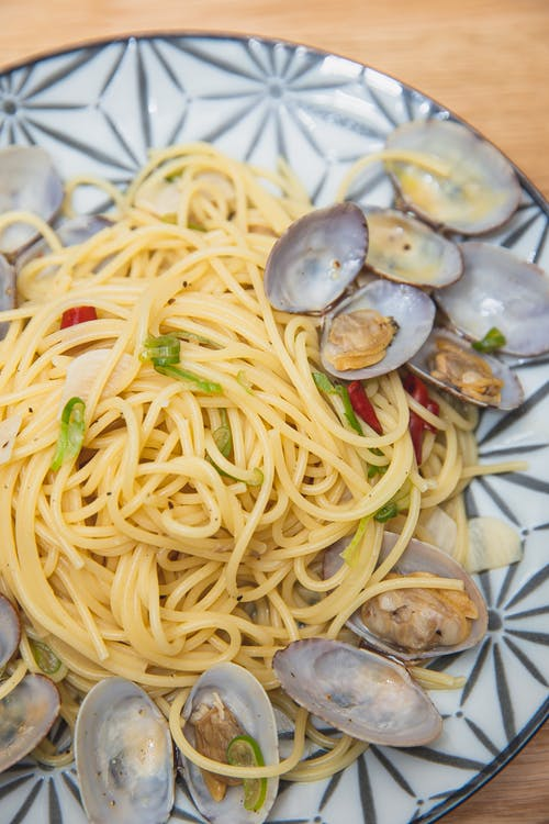Top view of tasty spaghetti with mussels topped with green onion and red pepper served on ceramic round plate and placed on table