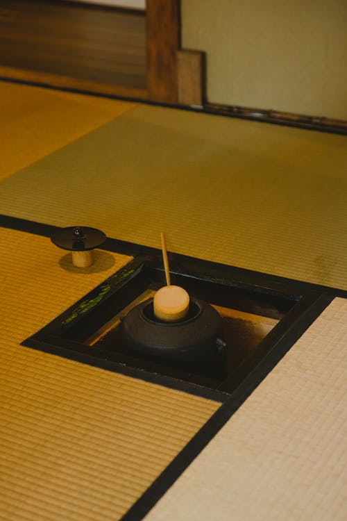 Authentic wooden hishaku used to transfer hot water to chawan placed on tatami in tea room during traditional Japanese ceremony
